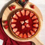 crostata alla marmellata di fragole e decorazione dei fragole su tagliere di legno